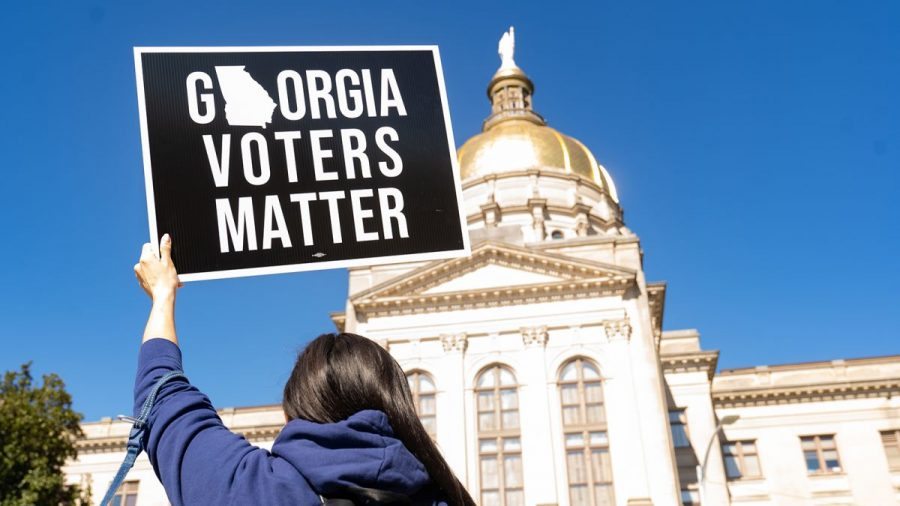 A protestor of the state bills which limit voting rights holds up a sign at the State Capitol.